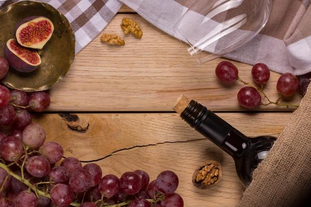 Flach mit einem gewitter aus roten trauben, einer flasche wein, einem glas und feigen Premium Fotos