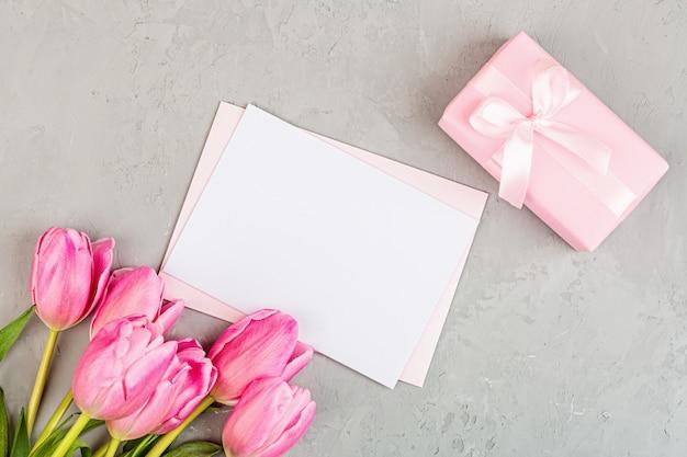 Flach mit tulpen und geschenkbox mit kopierraum auf grau liegen Premium Fotos