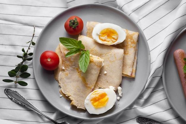 Flache crêpes mit hartgekochten eiern und tomaten Kostenlose Fotos