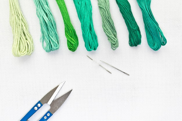 Flache draufsicht mit stickerei-leinwand, nadeln, fäden in grünen farben Premium Fotos