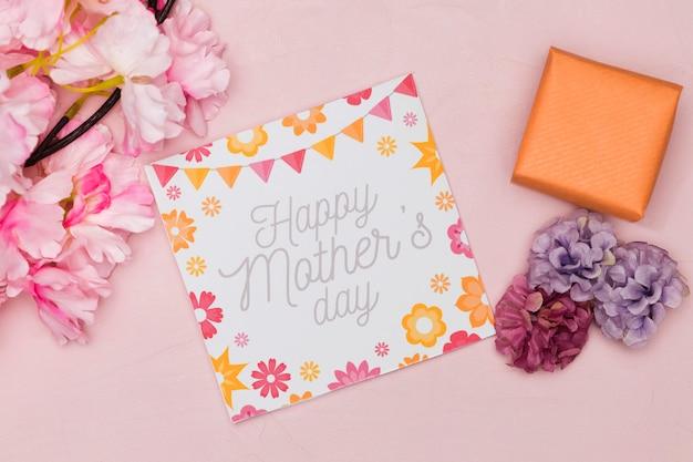 Flache karte und blumen für muttertag mit geschenk Kostenlose Fotos