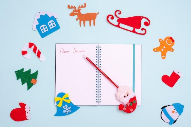 Flache komposition mit einem leeren offenen notizbuch mit der aufschrift lieber weihnachtsmann, ein stift mit weihnachtsmann und filz-weihnachtsdekorationen Premium Fotos