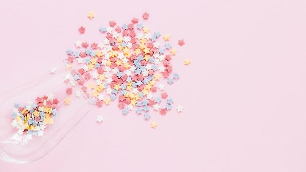 Flache lag bunte süßigkeit auf rosa hintergrund Premium Fotos