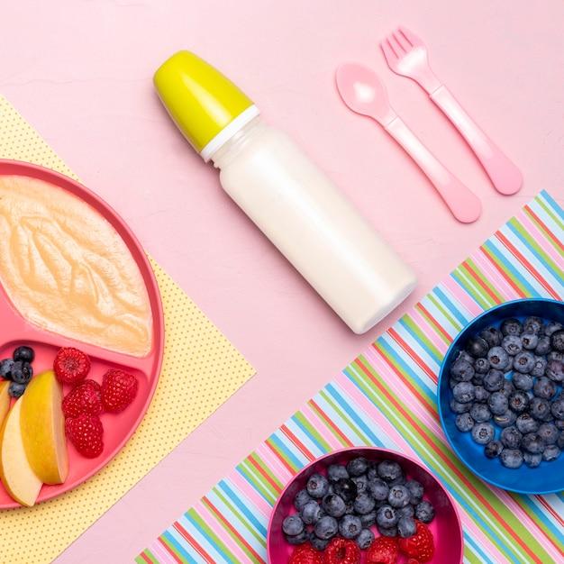 Flache lage der babyflasche und des essens mit früchten Kostenlose Fotos