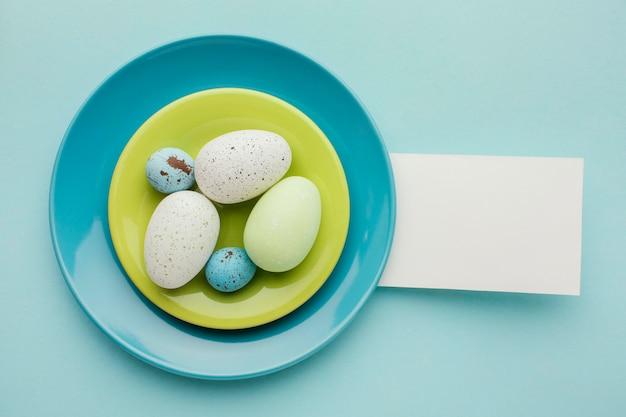 Flache lage der farbigen ostereier auf tellern mit papier Kostenlose Fotos