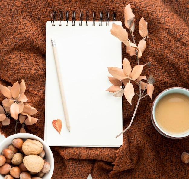 Flache lage der kaffeetasse mit herbstlaub und notizbuch Kostenlose Fotos
