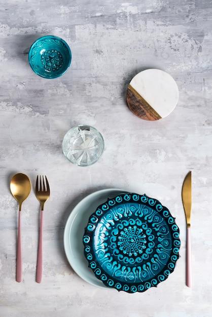 Flache lage der keramikplatte und der tischbesteckgeräte auf grau. leere platte. ,lebensmittel . Premium Fotos