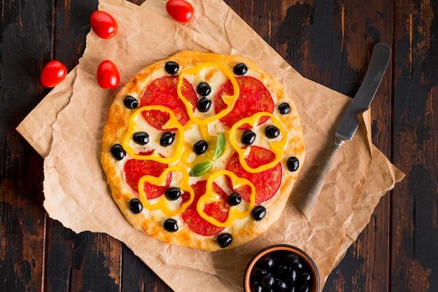Flache lage der köstlichen pizza auf holztisch Kostenlose Fotos