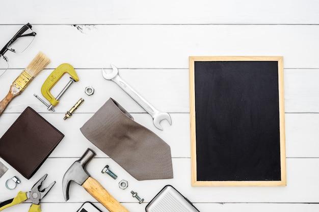 Flache lage der leerstellentafel mit handlichen werkzeugen und dem zubehör der männer des blauen kragens des baus über hölzernem hintergrund. Premium Fotos