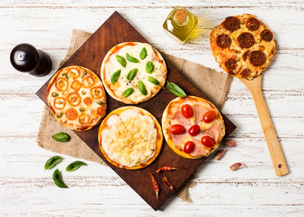 Flache lage der minipizza auf hölzernem behälter Kostenlose Fotos