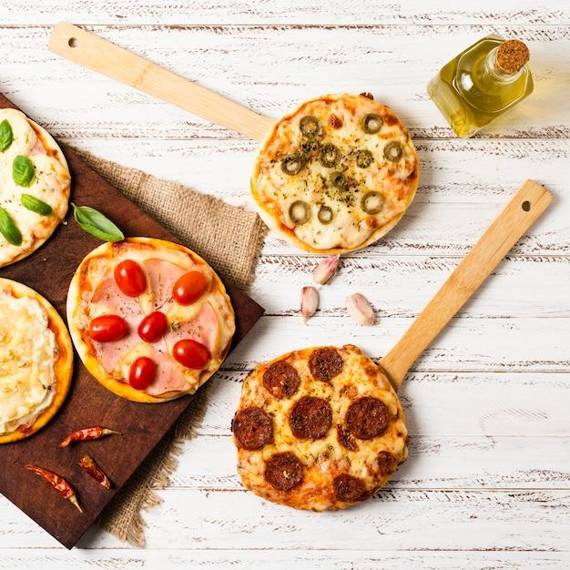 Flache lage der minipizza auf hölzernem behälter Premium Fotos