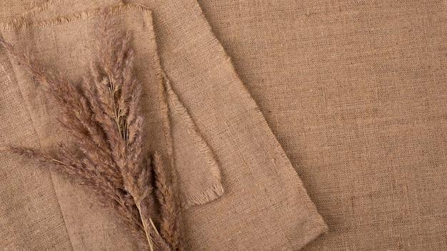 Flache lage der monochromatischen auswahl von textilien mit kopierraum und getrocknetem gras Kostenlose Fotos