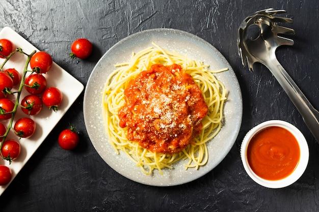 Flache lage der nudelplatte mit tomatensauce Kostenlose Fotos