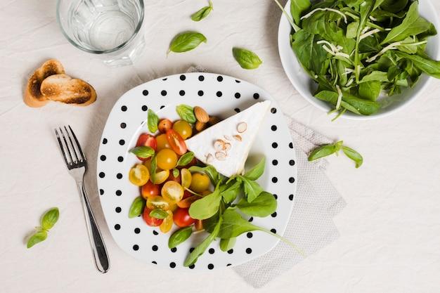 Flache lage der platte mit organischem gemüse und salat Kostenlose Fotos