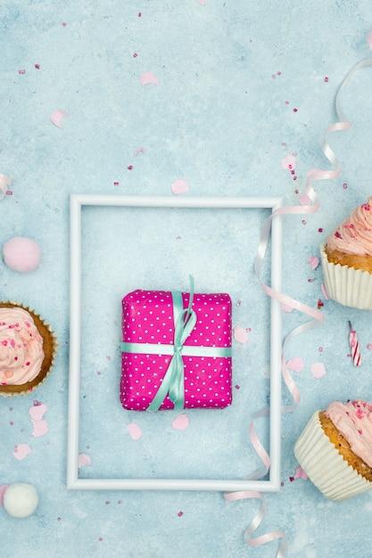 Flache lage des geburtstagsgeschenks mit kleinen kuchen und band Kostenlose Fotos