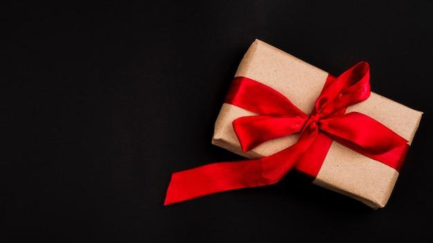 Flache lage des geschenks auf schwarzem hintergrund Kostenlose Fotos