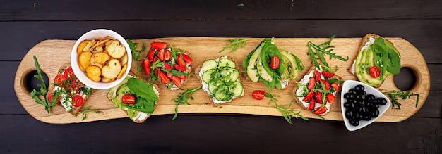 Flache lage des gesunden vegetarischen abendtisches. sandwiches mit tomaten, gurken, avocados, erdbeeren, kräutern und oliven, snacks. banner. sauberes essen, veganes essen Premium Fotos