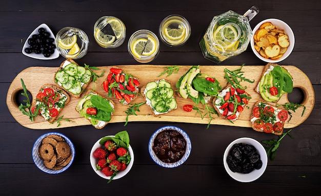 Flache lage des gesunden vegetarischen abendtischgedecks. sandwiches mit tomaten, gurken, avocados, erdbeeren, kräutern und oliven, snacks. sauberes essen, veganes essen Premium Fotos