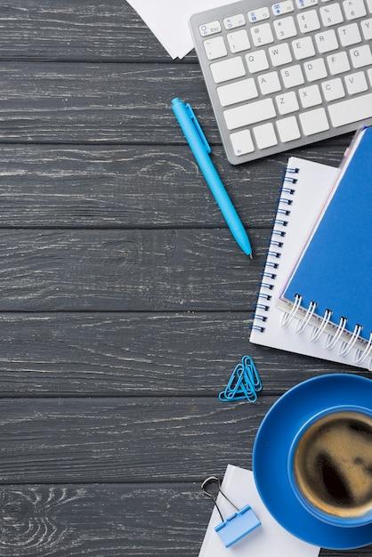 Flache lage des hölzernen schreibtisches mit kaffeetasse und tastatur Kostenlose Fotos