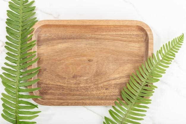Flache lage des holztabletts und der grünen blätter auf weißem marmorhintergrund. attrappe, lehrmodell, simulation Premium Fotos
