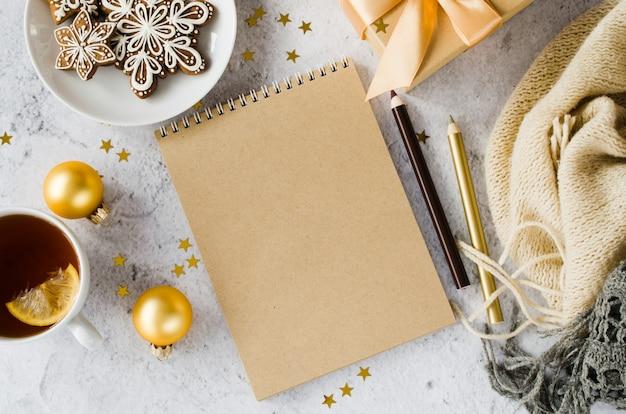 Flache lage des leeren braunen notizbuches mit geschenkbox, tee, plätzchen und plaid. Premium Fotos
