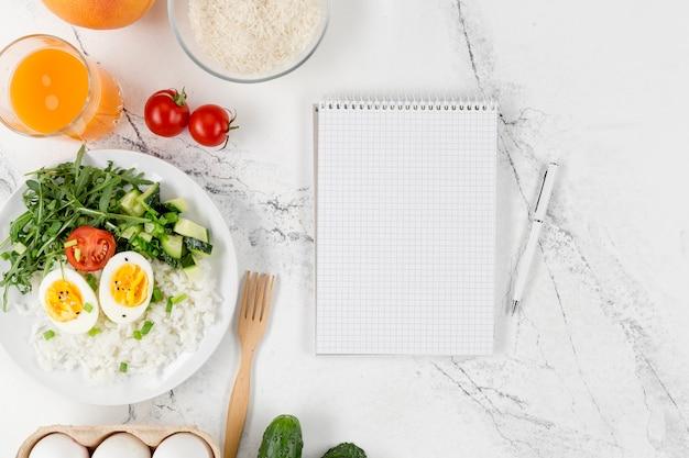 Flache lage des notizbuchs mit teller reis und eiern Kostenlose Fotos