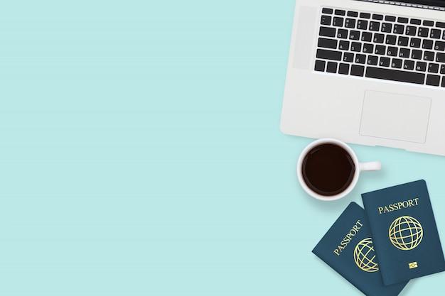 Flache lage des passes zwei, der kaffeetasse und des computerlaptops auf blauer pastellfarbe mit copyspace Premium Fotos