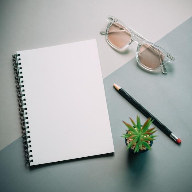 Flache lage des schreibtischs des minimalen arbeitsplatzes mit notizbuch, brillen und grünpflanze Premium Fotos