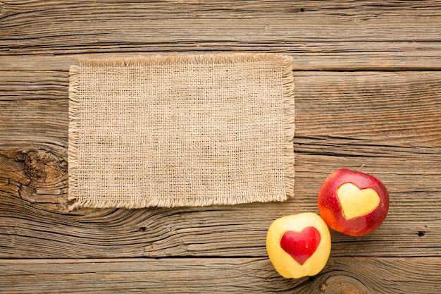 Flache lage des stoffes und der äpfel mit fruchtherzformen Kostenlose Fotos