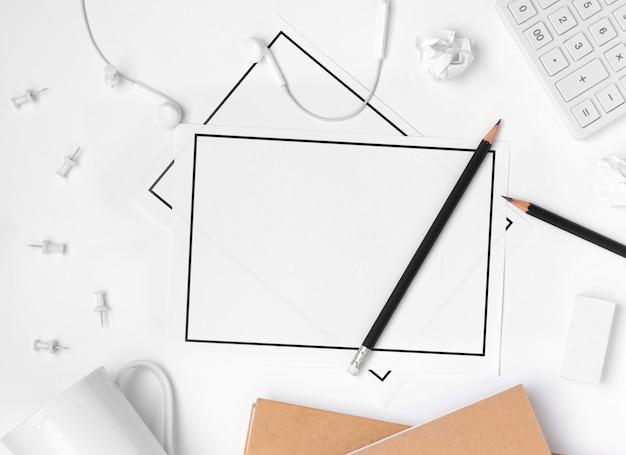 Flache lage des tischplattenarbeitsplatzzubehörs mit blatt des leeren papiers auf weißem hintergrund Premium Fotos