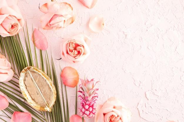 Flache lage des tropischen arbeitsplatzmodells mit palmmonsterablättern, rosa blumen, ananas und den blumenblättern auf pastell Premium Fotos