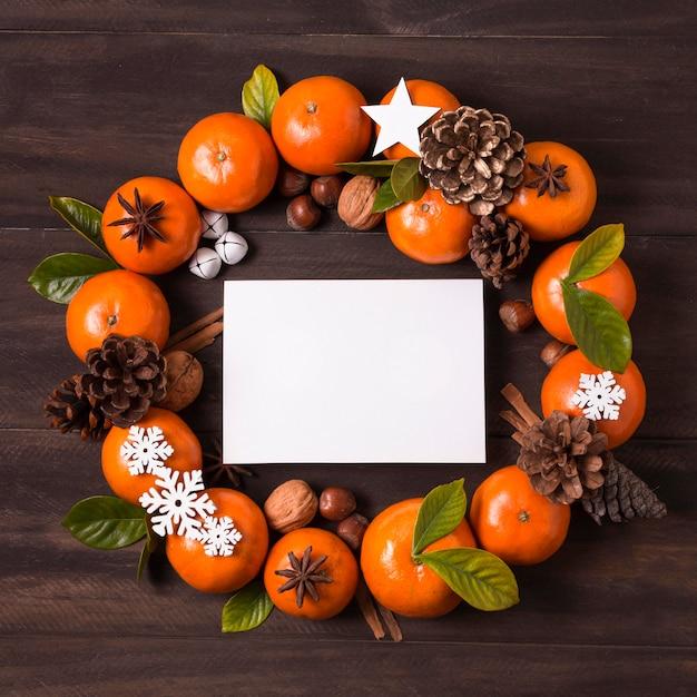 Flache lage des weihnachtskranzes machen von mandarinen und tannenzapfen mit leerem papier Kostenlose Fotos