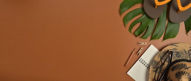 Flache lage, draufsichtarbeitsplatz mit augengläsern, notizbuch, hut, bleistift, grünem blatt, schuhen und kaffeetasse auf braunem hintergrund. Premium Fotos