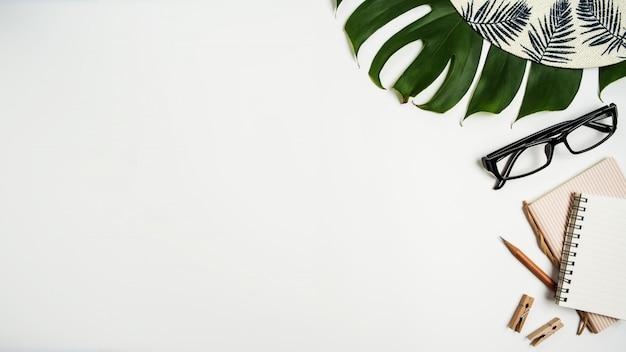 Flache lage, draufsichtarbeitsplatz mit augengläsern, notizbuch, hut, bleistift, grünem blatt, schuhen und kaffeetasse auf weißem hintergrund. Premium Fotos