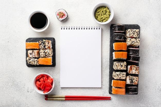Flache lage maki sushirollenzusammenstellung mit leerem notizbuch Kostenlose Fotos