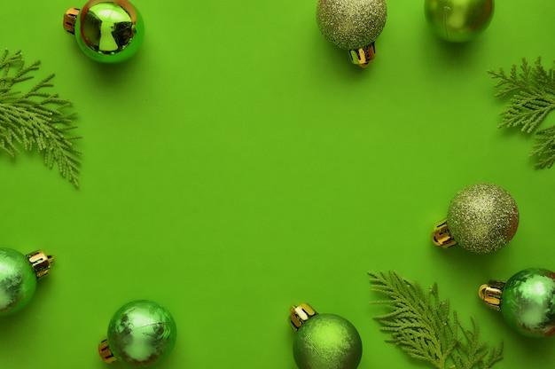 Flache lage, minimaler zusammensetzungshintergrund der draufsicht von grünen dekorativen weihnachtsverzierungen. Premium Fotos