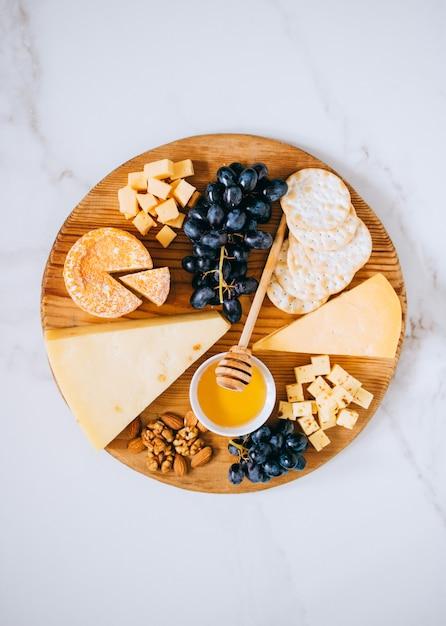Flache lage mit verschiedenen käsesorten, trauben, nüssen, honig und cracker in holzbrett auf marmor Premium Fotos