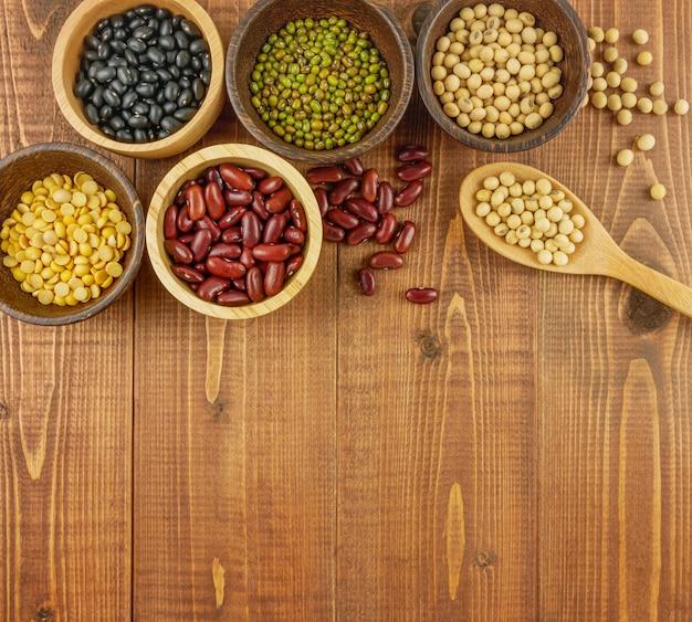 Flache lage, sortierte bohnen der draufsicht einschließlich rote bohne, sojabohnen, schwarze bohnen, mungobohnen auf braunem, beige hölzernem hintergrund Premium Fotos