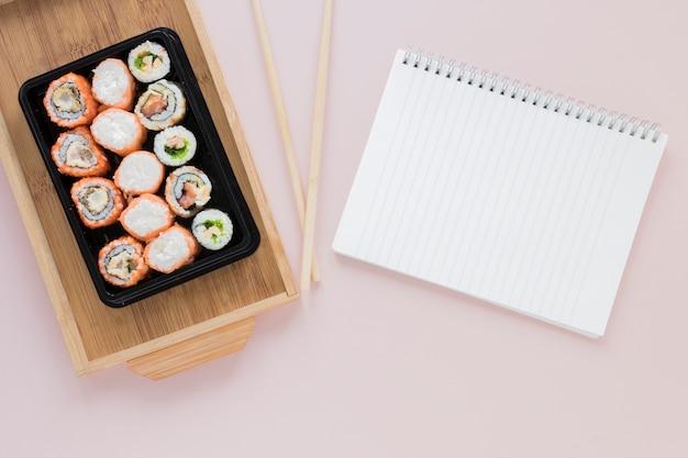 Flache lage sushi-komposition mit notizblock-vorlage Kostenlose Fotos