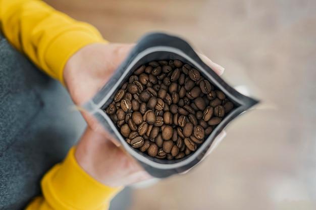 Flache lage von barista, die kaffeepaket hält Premium Fotos