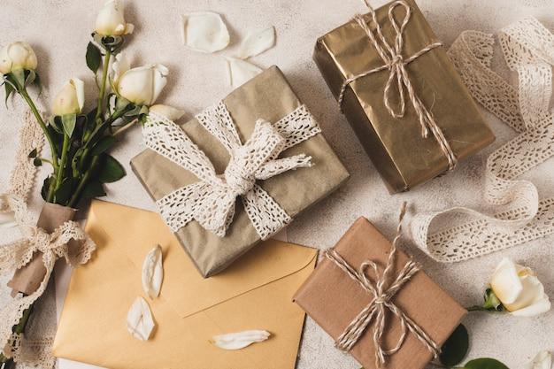 Flache lage von eleganten geschenken mit rosenstrauß Kostenlose Fotos