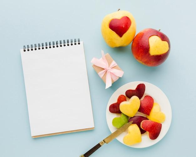 Flache lage von fruchtherzformen mit notizbuch und geschenk Kostenlose Fotos