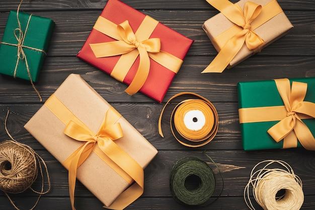 Flache lage von geschenkboxen für weihnachten auf hölzernem hintergrund Kostenlose Fotos