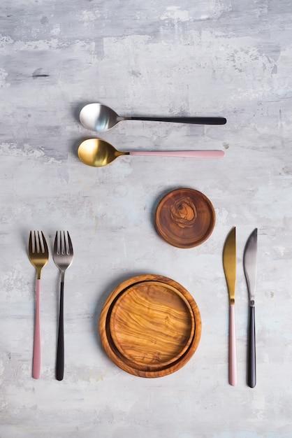 Flache lage von hölzernen platten- und tischbesteckgeräten auf grau. leere platte. , essen, kein abfall. Premium Fotos