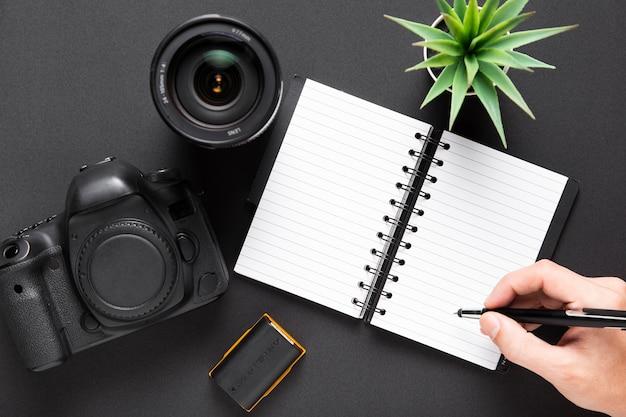 Flache lage von kameraobjektiven und von notizbuch auf schwarzem hintergrund Kostenlose Fotos