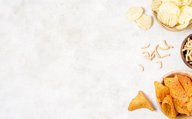 Flache lage von nacho-chips und kartoffelchips mit kopierraum Kostenlose Fotos