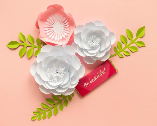 Flache lage von papierblumen mit blättern für frauentag Kostenlose Fotos