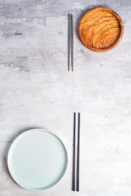 Flache lage von platten- und eisenstöcken auf grau. leere platte. , essen, kein abfall. Premium Fotos