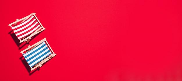 Flache lage von strandklappstühlen auf rotem hintergrund mit kopienraum. Premium Fotos