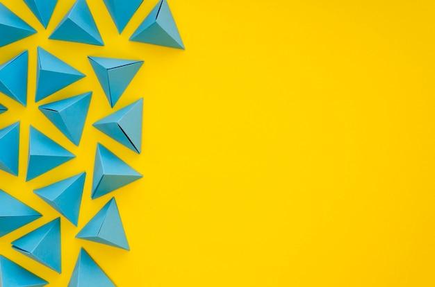Flache lage von vibrierenden pyramiden des farbigen papiers mit kopienraum Kostenlose Fotos